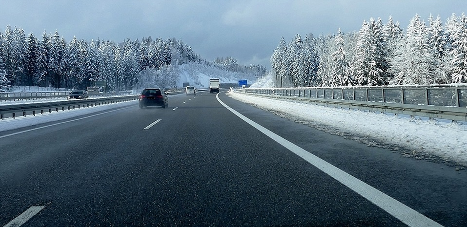 carretera con un coche y nieve alrededor