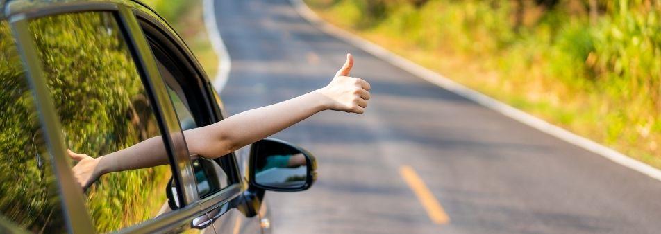 Mujer en un coche haciendo una señal